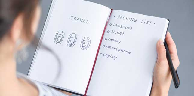 Writing Packing List in Notebook