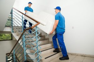 Removals men carry furniture up the stairs