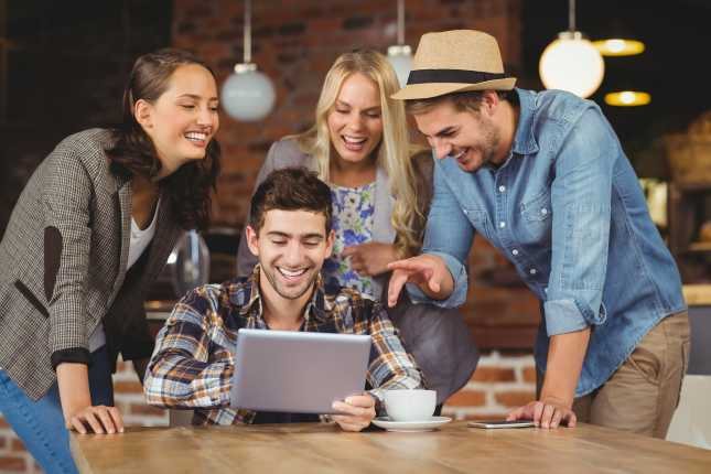 Laughing friends looking at tablet computer at coffee shop
