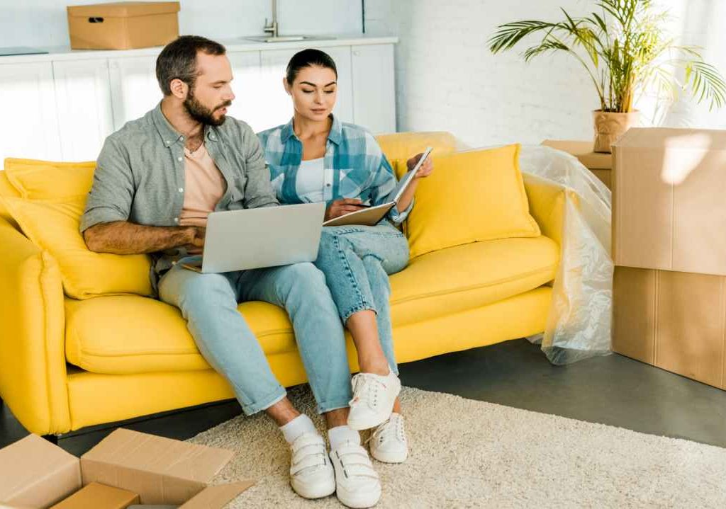 Removals Loughton, Smart couple on sofa planning a home move