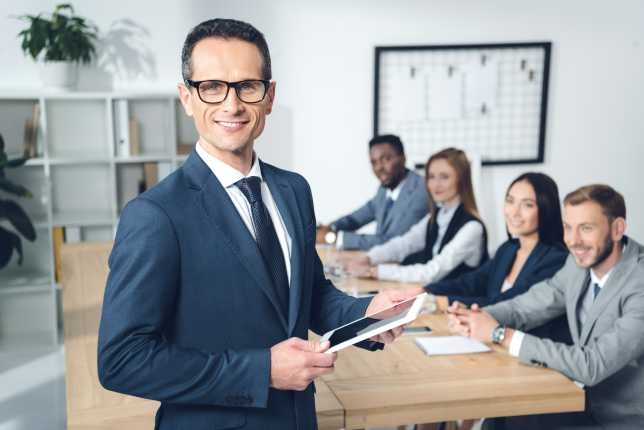 Business man smiling with colleagues behind