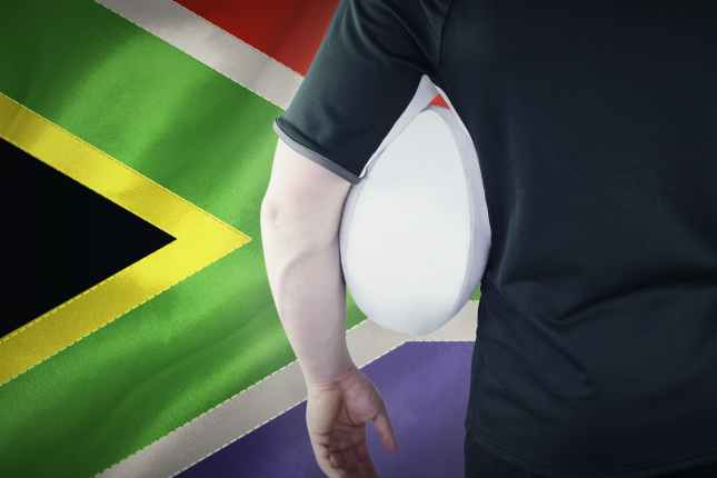 Rugby player holding a rugby ball by South Africa flag